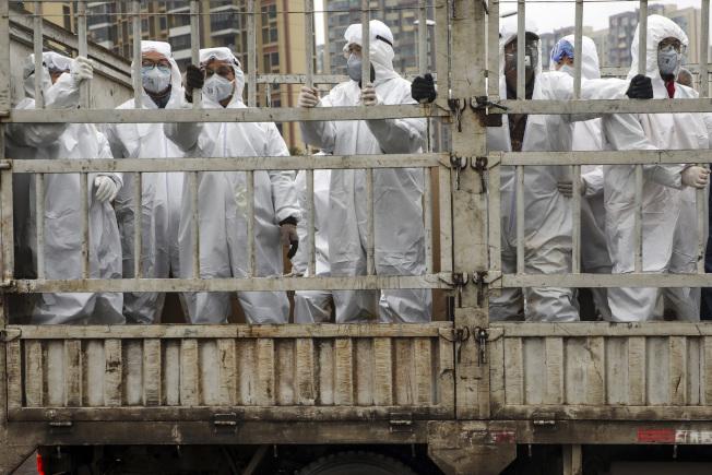 醫護人員穿上全套防護衣,攜帶醫療物資趕往武漢火神山醫院。(美聯社)