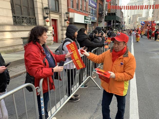遊行工作人員給民眾發放寫有「武漢加油」的手幅。記者和釗宇/攝影