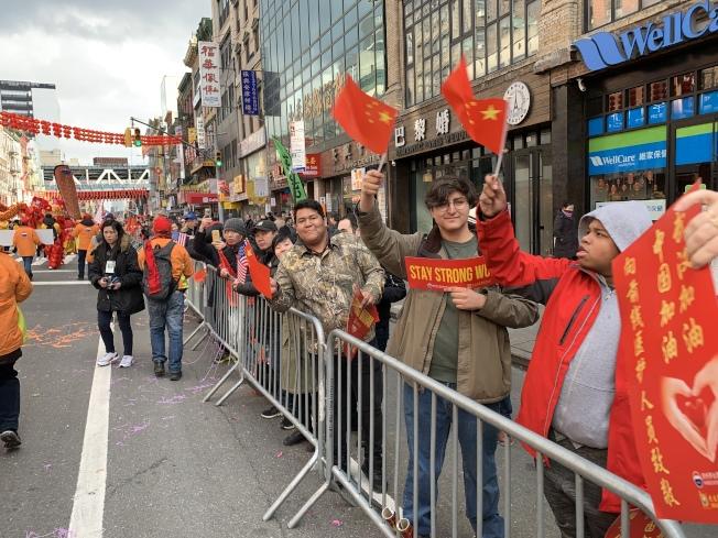 """今年观看游行的民众有所减少,但不少围观的各族裔民众打出""""武汉加油""""标语。(记者和钊宇/摄影)"""