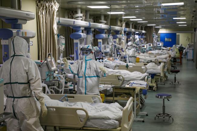 武漢醫護人員穿著全套防護服照顧新冠肺炎的重症病人。(路透)