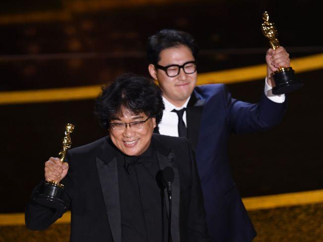奉俊昊(左)和另一名編劇韓進元上台領獎,十分激動。(Getty Images)