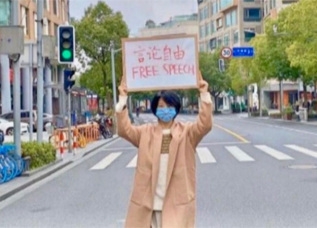 李文亮醫師頭七前夕,一位上海女青年高舉言論自由標牌走上大街。(圖:讀者提供)