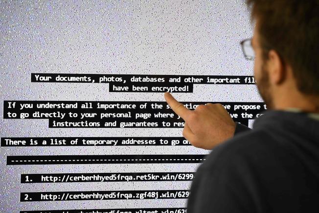 許多公司被駭客入侵電腦系統後,毫無辦法,多數交納勒索費。但多數駭客拿錢就失蹤,被駭公司資料系統仍未解除困境。圖為在法國的國家電腦科學與自動化研究所上的大電腦屏幕,顯示被駭的頻面。(Getty Images)