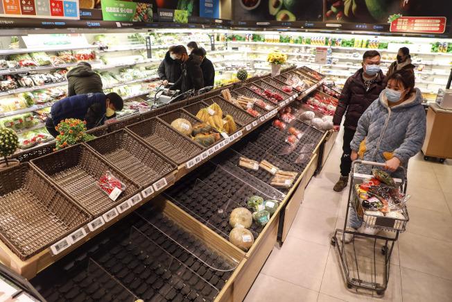 疫情後,中國各地物價出現上漲現象。圖為重疫區武漢市民10日帶著口罩出門,到超市購買生活必需品。( Getty Images)