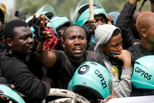 多名司機在拉哥斯議會外抗議「摩托車禁令」。(路透)