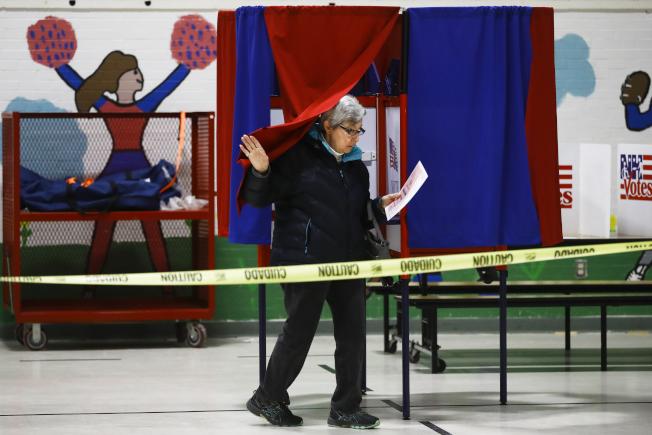 一位婦人剛投完票,掀開幕布離開投票站。(美聯社)