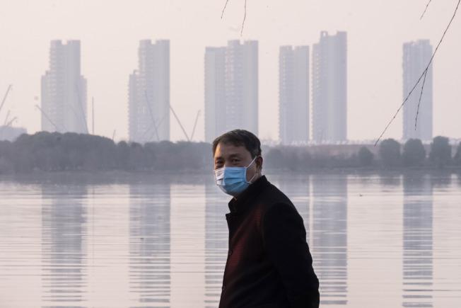 武漢,一名男子戴口罩站在江邊。(美聯社)