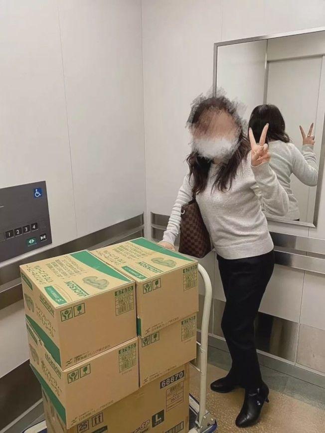 中国女业务从医院搬走口罩等医疗物品开心留影。(取材自「东京新青年」微信公众号)