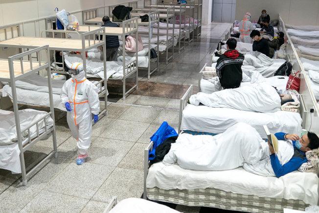 穿着防护服的医护人员在照顾冠状病毒患者。路透