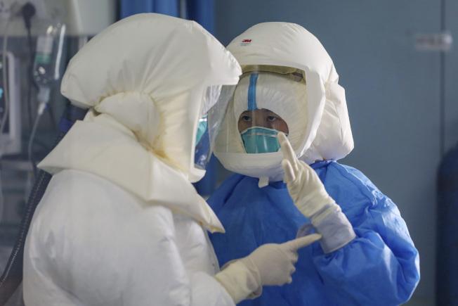 13日,湖北武漢金銀潭醫院,醫護人員全身穿好防護服,照顧新冠肺炎重症患者。(美聯社)