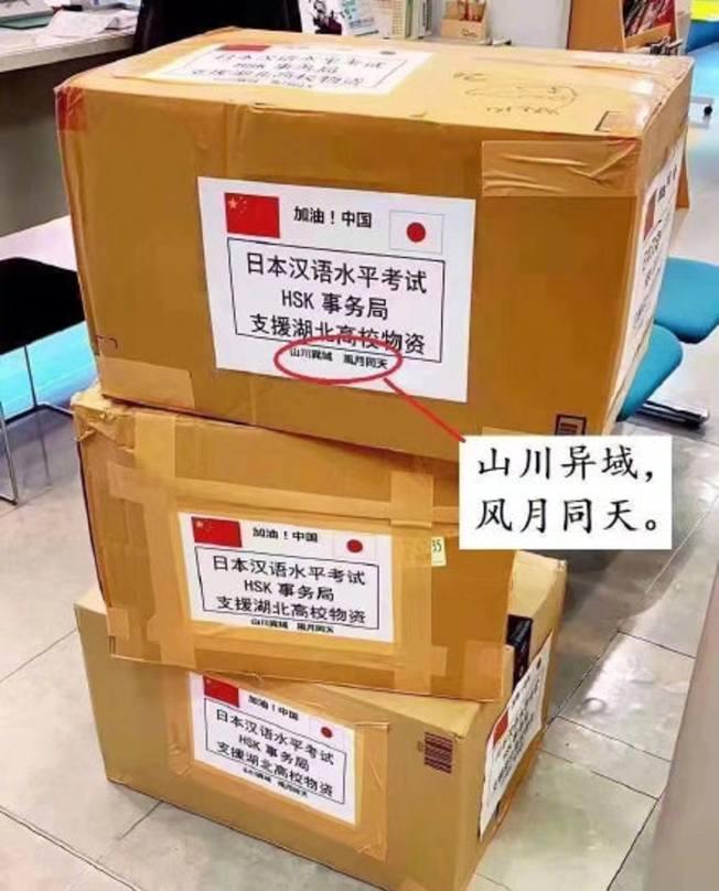 日本各界捐助中國的醫療物資,不少紙皮箱上都寫有言簡意賅的詩詞,圖為取自日本國長屋王的佛偈「山川異域,風月同天」。(微博)