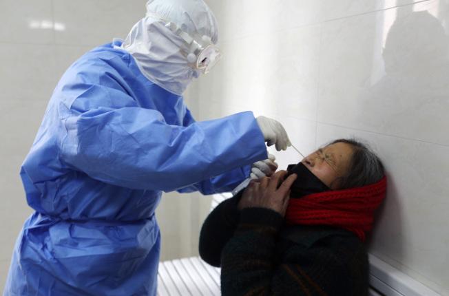 山東一名醫生從病患呼吸道採取檢體,檢驗是否含有新冠病毒。(美聯社)