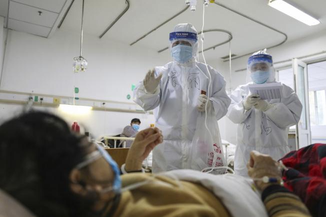 (備用)武漢是此次疫情的中心,圖為醫生為收治的病患做檢查。(美聯社)