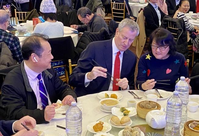 白思豪(中)在法拉盛中餐館練習用筷子夾菜,左為杜彼得。(記者朱蕾/攝影)
