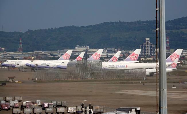 受新冠肺炎疫情對營運的影響,華航13日宣布主管減薪10%,桃園機場內也至少有7架飛機停放在維修廠棚外待命。(記者鄭超文/攝影)