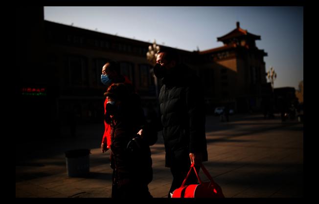 一向熙來攘往的北京火車站,因疫情顯得冷清。出行乘客個個不忘戴上口罩。(路透)