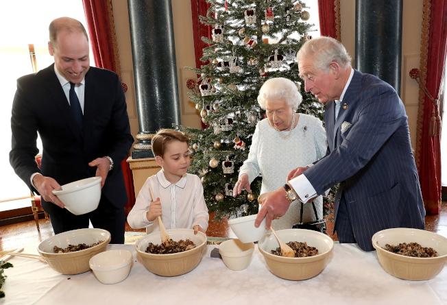 英國王室2019年12月22日發布照片,女王和王室嫡長子繼承人做耶誕布丁。左起,女王長孫威廉、長曾孫喬治、女王和王儲查理。(歐新社)