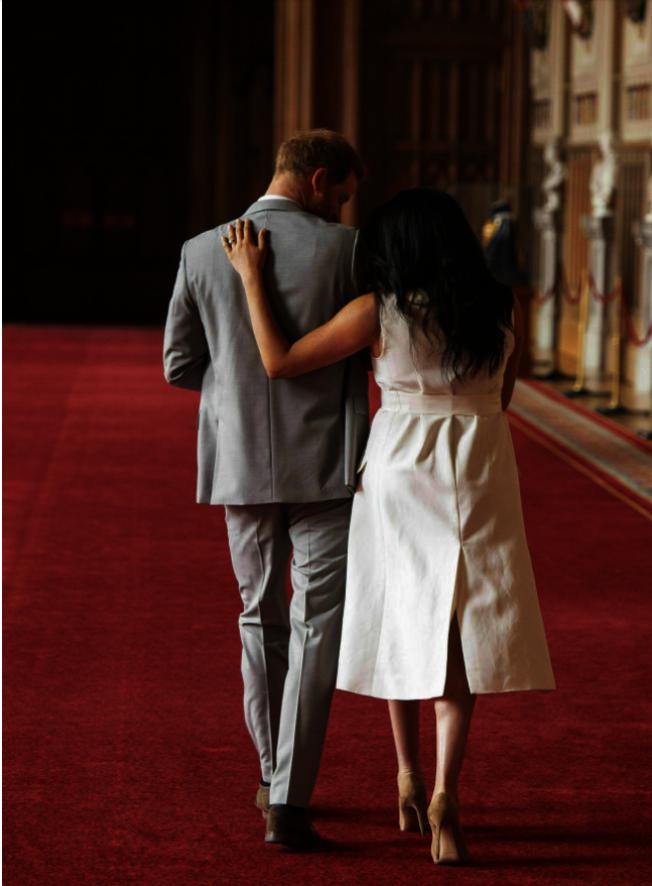 哈利王子與梅根馬克爾在兒子亞契出生後,在溫莎堡和媒體會面。結束後兩人抱著兒子走回室內。(美聯社)