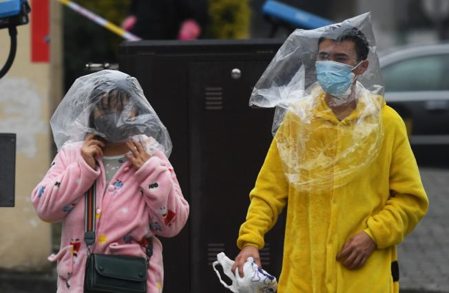 受新冠肺炎疫情影響,重慶大渡口街頭兩位市民14日身穿睡衣,頭戴保鮮袋出行。(中新社)