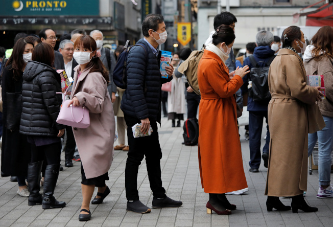 日本民眾14日在東京藥房門口排隊買口罩。(路透)