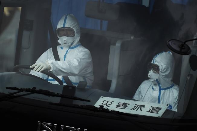 一輛公車14日從橫濱碼頭駛出,駕駛(左)全副裝備將鑽石公主號郵輪老年乘客轉移到日本政府指定的住所。 (Getty Images)