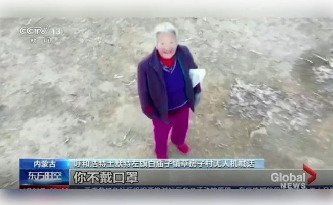 無人機盤旋在一名老婦頭上,用擴音器告訴她要戴口罩防疫。(取材自Global News)