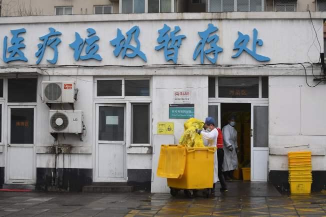 大批中國醫護人員遭到新冠病毒感染,圖為北京一家地區醫院人員處理醫療垃圾。(Getty Images)