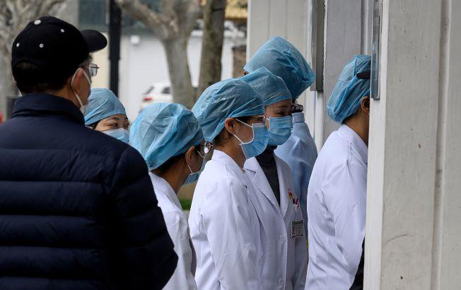新冠病毒在中國擴散,圖為上海醫護人員排隊進入一家社區醫院。(Getty Images)