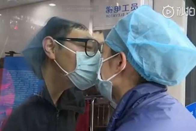 戴口罩、穿著全身防護衣,這對醫護夫妻隔著病房玻璃為彼此獻吻,傳遞思念之情。(取材自微博)