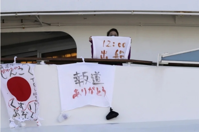 鑽石公主號郵輪上一名婦女手持布條,寫著出發時間,旁邊的標語上寫著「藥品短缺」、「感謝報導」字樣。(美聯社)