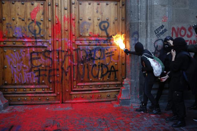 墨西哥總統府的大門上,14日被噴上了「殺女之國」的大字。(美聯社)