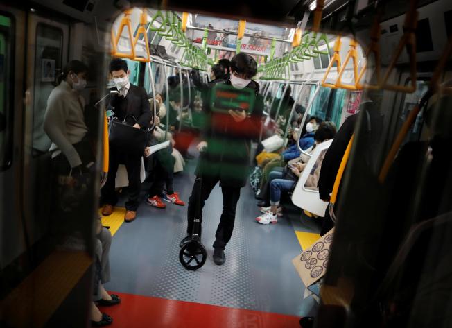 日本厚生勞動大臣加藤勝信昨坦承,新冠肺炎疫情「難以避免會在日本國內蔓延」。圖為東京一列地鐵車廂內,乘客因擔心感染,都載著口罩。(路透)