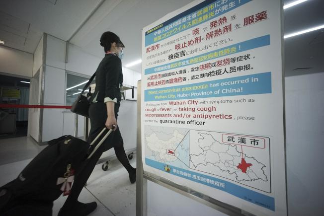 日本疫情有升高趨勢,圖為一名空姐走過東京成田機場一個新冠病毒肺炎公告板。(美聯社)