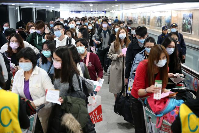 新冠肺炎疫情持續擴大,日本東京、名古屋等地皆出現多名確診,入境台灣的旅客必須填寫健康聲明書,讓入境處大排長龍。(記者鄭超文/攝影)