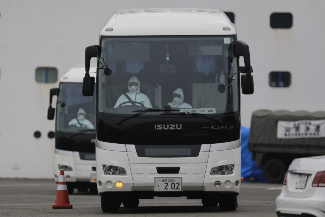 美國宣布將從停靠日本橫濱的郵輪鑽石公主號接回美籍乘客,圖為巴士載船上患者離開碼頭。(美聯社)