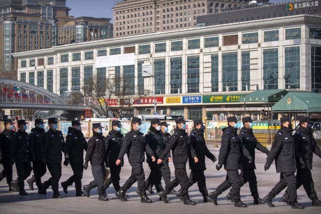 為維穩防疫,中國出動大量軍警,圖為警員戴口罩在北京火車站外面巡邏。(美聯社)