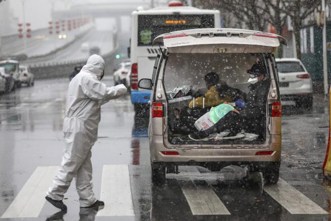 為維穩防疫,中國採取嚴格管制措施,圖為政府人員在湖北武漢檢查過往車輛。(美聯社)