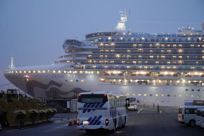 幾輛窗簾緊閉的巴士,16日開向鑽石公主號郵輪停靠的日本橫濱港。(Getty Images)