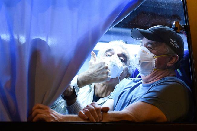 停靠在日本橫濱港的郵輪「鑽石公主號」的美國公民,17日凌晨乘坐專車前往羽田機場返美,其中一人隔著車窗向外豎起大拇指。(美聯社)