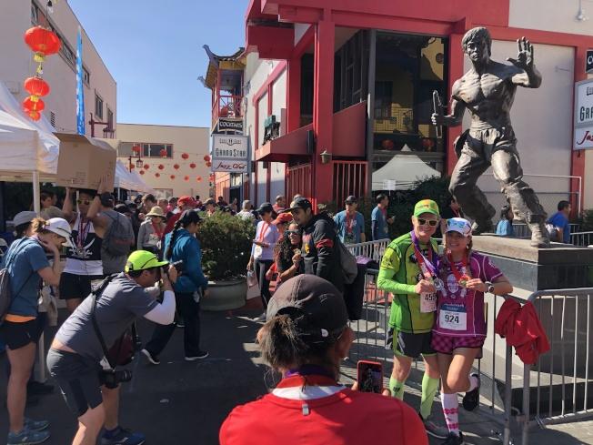 爆竹賽跑完賽的選手們在李小龍雕像前拍照留念。(記者李雪/攝影)