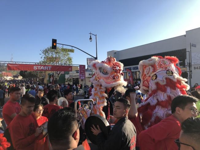 舞獅隊和太鼓隊在道路兩側為選手們加油。(記者李雪/攝影)