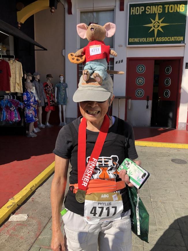 69歲的華裔選手趙汝謙頭戴自製老鼠帽子,老鼠胸口也別有和她一樣的號碼牌,引得許多人都要求拍照。(記者李雪/攝影)