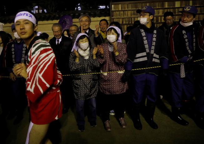 日本岡山縣西大寺觀音院15日照常舉行年度「裸祭」,超過1萬名不畏嚴寒的壯丁打赤膊爭奪能帶來福氣的「寶木」。不少人戴口罩參觀。(路透)