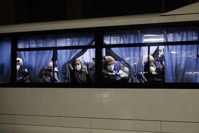 停靠在日本橫濱港的郵輪「鑽石公主號」上的美國公民,17日凌晨乘坐專車前往羽田機場返美。(美聯社)