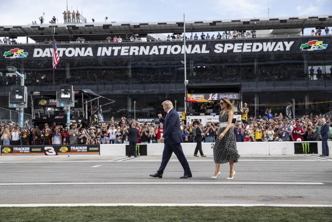 川普總統與第一夫人梅蘭妮亞16日參加佛州岱通納500賽車競賽,開始前向全場車迷揮手致意。(美聯社)