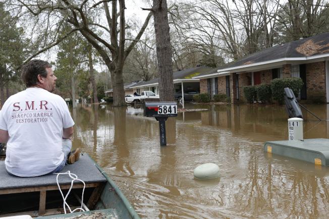 密西西比州連日豪雨導致河水暴漲。圖為首府傑克森市一男子乘坐小艇查看社區災情。(美聯社)