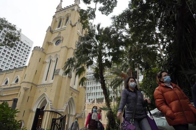 參加香港聖約翰天主教堂彌撒的教徒都戴著口罩,和他人保持距離。(美聯社)