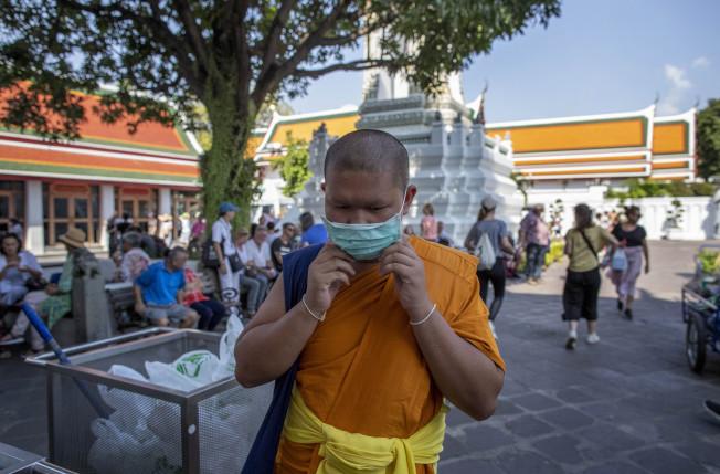泰國百年古剎臥佛寺因新冠肺炎疫情,遊客大量減少。一名臥佛寺僧侶戴上口罩自保。(美聯社)