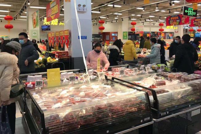 新冠肺炎情蔓延全球,圖為重災區湖北武漢市民佩戴口罩,在超市購買蔬果、生活用品等物資。(中新社)