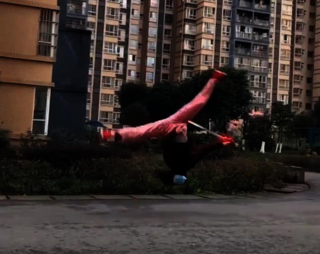 視頻中,一名戴著口罩的女子走出樓棟單元門:左手是紙箱,右手則拿著一柄長劍。 將紙箱扔進垃圾箱後,她往前一個衝跑,然後空翻雙腿呈一字,落地後又行雲流水地舞起寶劍。(視頻截圖)